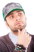 Handsome Bearded Guy in Cap Touches Chin Looks upward - stock photo