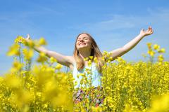 Young happy woman on blooming rapeseed field Stock Photos