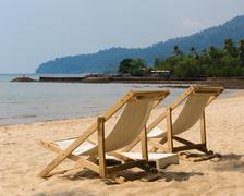 Stock Photo of Two beach chairs on idyllic tropical sand beach.