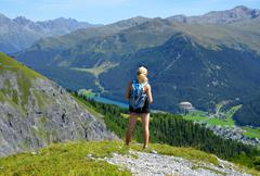 Hiker looks at the alpine city Davos. - stock photo