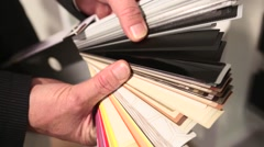 Close up of hands scrolling through a color guide. Stock Footage