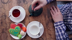 A man pours tea. Vintage table, collorful cookies Stock Footage
