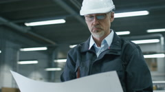 Senior engineer in hardhat is standing in a factory and looking at a blueprint - stock footage