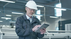 Senior engineer in hardhat is using a tablet computer in a factory - stock footage