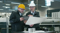 Two engineers discuss a blueprint while checking information on a tablet Stock Footage