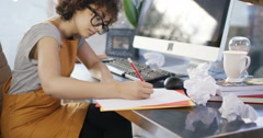 4K Young woman working at desk in home office with crumpled pieces of paper - stock footage