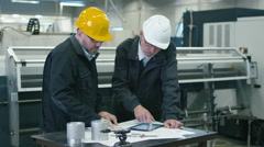 Two engineers discuss a blueprint while checking information on tablet computer Stock Footage