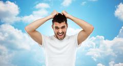crazy shouting man in t-shirt over blue sky - stock photo