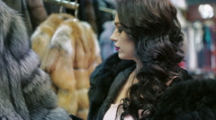 Glamorous woman looking on the fur coat in the shop Stock Footage