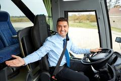 Happy driver inviting on board of intercity bus Stock Photos