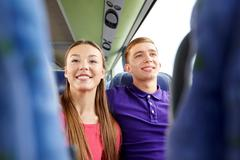 Stock Photo of happy teenage couple or passengers in travel bus