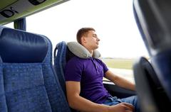 Happy young man sleeping in travel bus with pillow Stock Photos