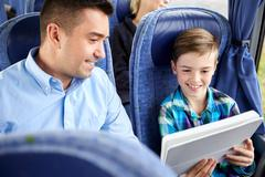 Happy family with tablet pc sitting in travel bus Stock Photos