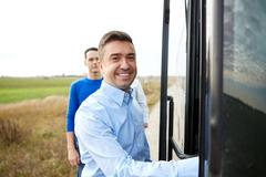 Group of happy male passengers boarding travel bus Stock Photos