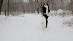 Young girl playing with a dog in winter park. Slow motin Stock Footage