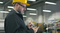 Senior engineer in hardhat is using a tablet computer with a stylus in a factory - stock footage
