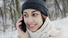 Beautiful girl talking on a smartphone in the winter park Stock Footage