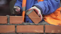 Builder puts a brick building wall - stock footage