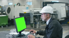 Senior engineer in glasses is working on a desktop computer with a green screen Stock Footage