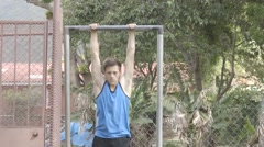 Man Doing Pull-ups with Extended Legs - stock footage