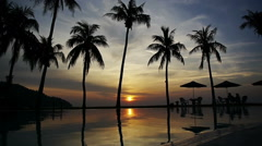 Sun setting reflected in pool water under the palm trees in a tropical resort Stock Footage