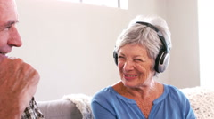 Mature couple listening to music with headphones on the couch Stock Footage