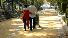 Stock Video Footage of Young family walking with stroller in the city park, super slow motion