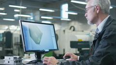 Senior engineer in glasses is working on a desktop computer in a factory Stock Footage