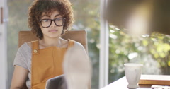 4K Young woman sitting at desk in home office, using computer & having drink Stock Footage