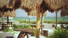 Straw tiki styled tables at a tropical beach resort Stock Footage