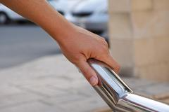 Woman hand on handrail - stock photo