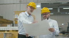 Two employees at logistics center warehouse talk about the plan on white paper - stock footage