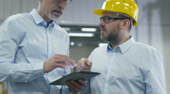 Two employees are discussing work with tablet computer at logistics center - stock footage