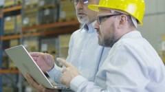 Two employees at logistics center are discussing work while holding a laptop - stock footage