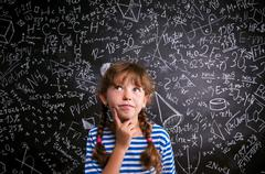 Girl  thinking, finger on cheek, blackboard with mathematical sy - stock photo