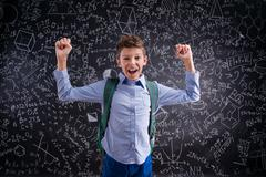 Excited and victorious boy against blackboard with mathematical - stock photo