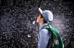 Boy  with schoolbag against big blackboard with mathematical sym - stock photo