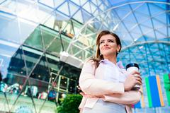 Businesswoman with coffee cup against glassy modern office build Stock Photos