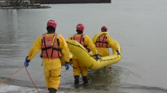 Firefighters Training in Ice Suit Launch Boat into Lake Stock Footage