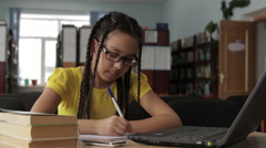 Girl with long hair wearing glasses working in the school library. Stock Footage
