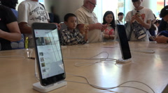 People try out iPhones in the Apple store in Beijing, consumption in China - stock footage