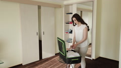 beautiful girl shifts things out of the closet in a suitcase - stock footage