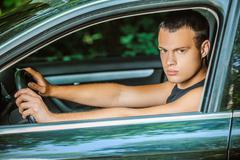 portrait of young man driving car - stock photo
