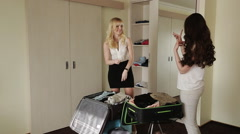 cute girlfriend shift things out of the closet in a suitcase - stock footage