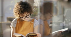 4K Portrait of young woman reading a book at home. Stock Footage