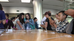 Asian customers try out a iPhones products in the Apple store in Beijing, China - stock footage