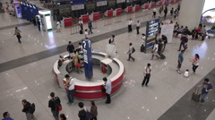 People ask questions at an information booth at Beijing International Airport Stock Footage