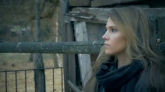 Beautiful woman standing near fence very concerned look, tracked shot - stock footage