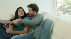 Cute happy couple talking about furnishing home looking on tablet new furniture Stock Footage