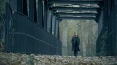 Beautiful woman walking across iron bridge low angle shot - stock footage